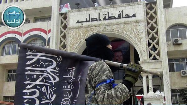 A fighter from Syria's al-Qaida-linked Nusra Front holds his group flag as he stands in front of the governor building in Idlib province, north Syria. - Sputnik International