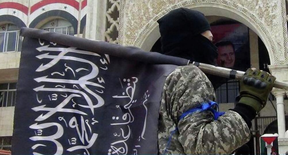 A fighter from Syria's al-Qaida-linked Nusra Front holds his group flag as he stands in front of the governor building in Idlib province, north Syria.