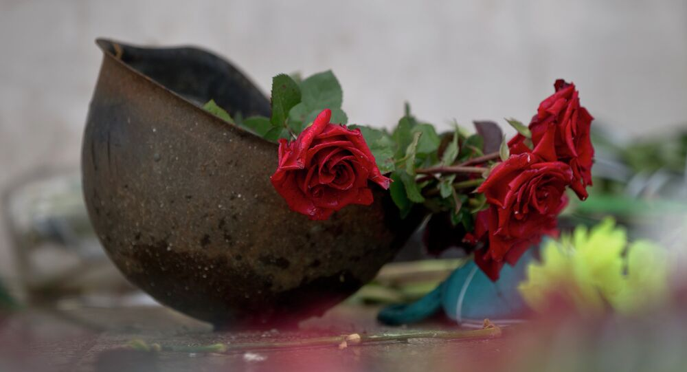 Roses lay in an old military helmet outside the burnt trade union building where more than 40 people perished in a fire on May 2, 2014
