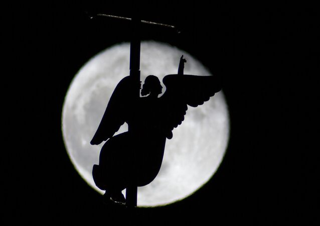 In this photo taken through a telescope lens, the city landmark, a weather vane in the form of an Angel, is fixed atop a spire of the Saints Peter and Paul Cathedral, as it is silhouetted on the rising moon in St.Petersburg, Russia