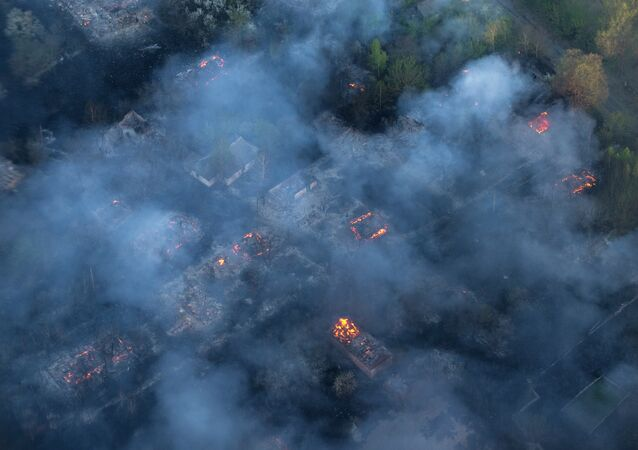 Fire hits an abandoned village in the exclusion zone around Chernobyl, Ukraine, Tuesday, April 28, 2015, as fire has engulfed a large sector of woods in the exclusion zone around the destroyed Chernobyl nuclear power plant. Ukrainian Prime Minister Arseniy Yatsenyuk says the fire is being brought under control.