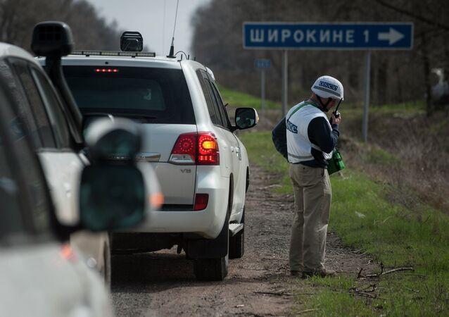 An OSCE observer speaks via radio, in front of the sign saying Shyrokyne, near the village of Shyrokyne, eastern Ukraine