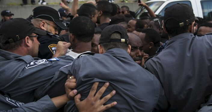 Israeli policemen push protesters, mainly whom are Israeli Jews of Ethiopian origin, during a demonstration against what they say is police racism and brutality, after the emergence last week of a video clip that showed policemen shoving and punching a black soldier during a protest in Tel Aviv May 3, 2015.