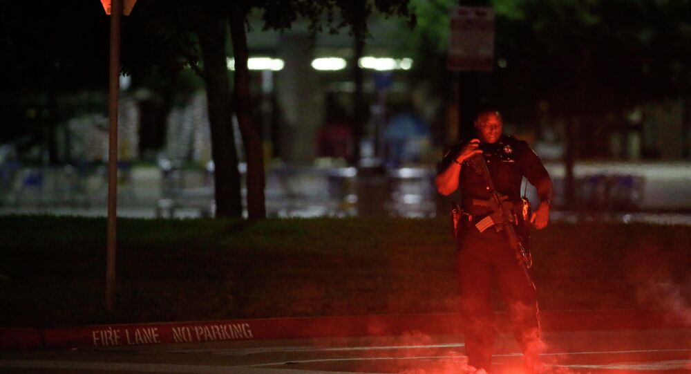 An armed police officer stands guard at a parking lot near the Curtis Culwell Center