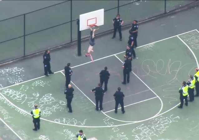 Shirtless man removed from basketball hoop