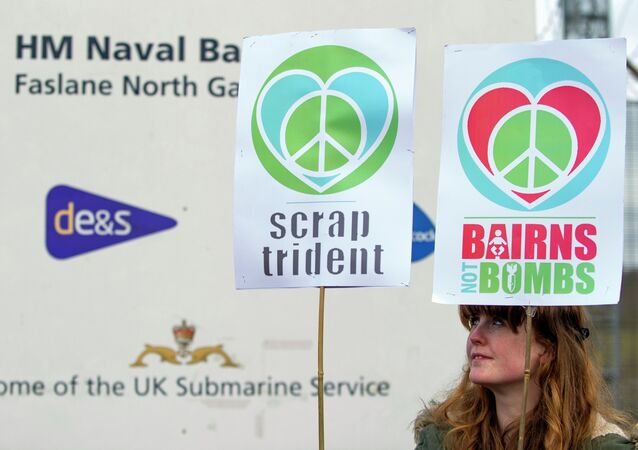 A protester calling for an end to the Trident nuclear programme holds placards at a blockade in the road in front of HM Naval Base Clyde in Faslane, Scotland, northeast of Glasgow, on April 13, 2015 the UK base for Trident.