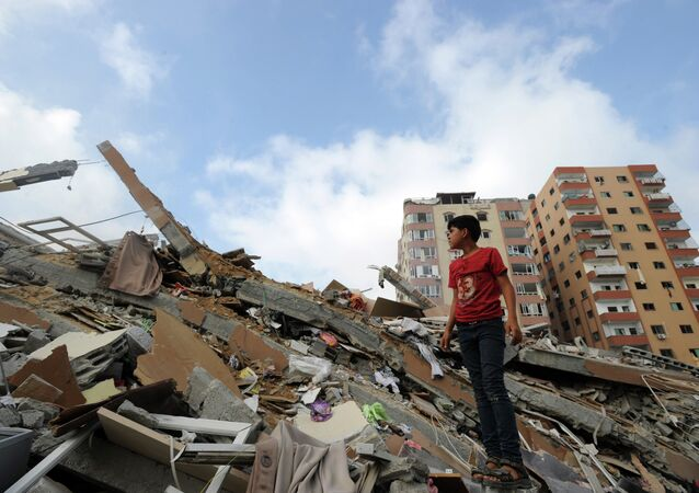 Palestinians collect their belongings from under the rubble of a residential tower, which witnesses said was destroyed by an Israeli air strike in Gaza.