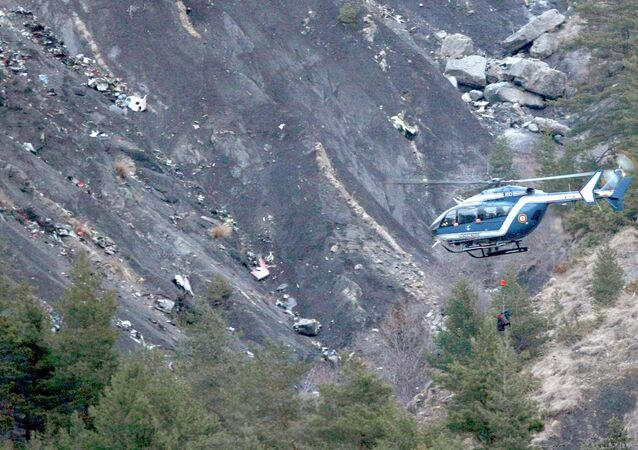 A rope hangs from a rescue helicopter flying past debris of the Germanwings passenger jet, scattered on the mountainside, near Seyne les Alpes, French Alps