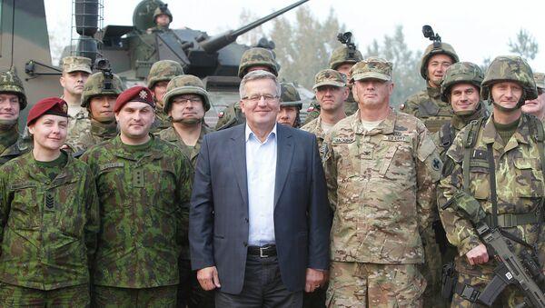 Poland's President Bronislaw Komorowski stands with troops from Poland and other nations in Bemowo Piskie near Orzysz, in northeastern Poland - Sputnik International