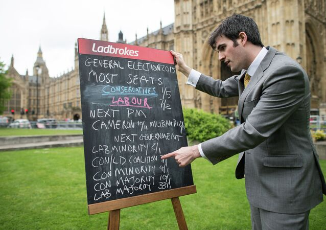 A bookmaker displays the latest odds on the result of the upcoming UK general election outside the Houses of Parliament in central London on May 6, 2015