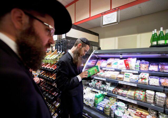 Orthodox Jewish men check kosher food at a supermarket in Berlin