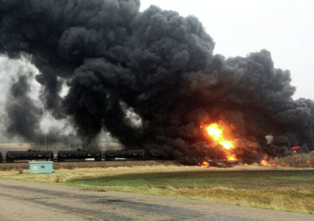 Smoke and fire rise from an oil train that derailed, Wednesday, May 6, 2015, in Heimdal, N.D.