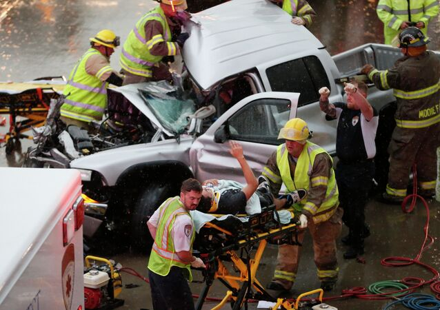 The driver of a truck which crashed during severe weather on Interstate 35 gestures to his rescuers after being cut from the truck in Moore, Okla., Wednesday, May 6, 2015