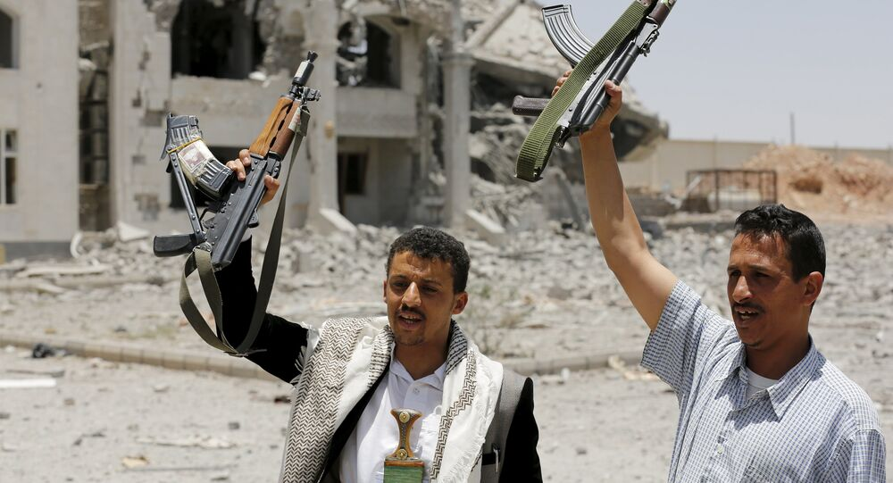 Houthi militants gesture in the yard of the residence of the military commander of the Houthi militant group, Abdullah Yahya al Hakim, after it was hit by an airstrike, in Sanaa April 28, 2015