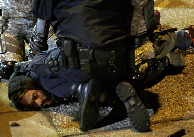 A protester is taken into custody in Ferguson, Mo.