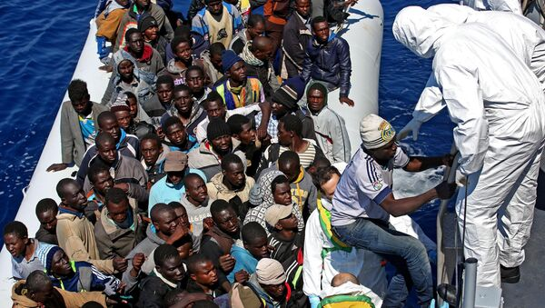 Migrants crowd and inflatable dinghy as rescue vassel  Denaro  of the Italian Coast Guard approaches them, off the Libyan coast, in the Mediterranean Sea, Wednesday, April 22, 2015 - Sputnik International