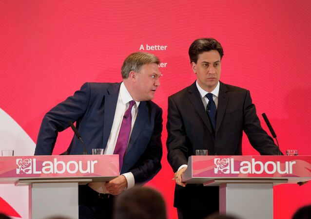 The leader of Britain's Labour Party Ed Miliband, right, listens to his party's finance minister Ed Balls during an election campaign press conference on their theme of the threat to family finances from Britain's Conservative Party in London, Wednesday, April 29, 2015