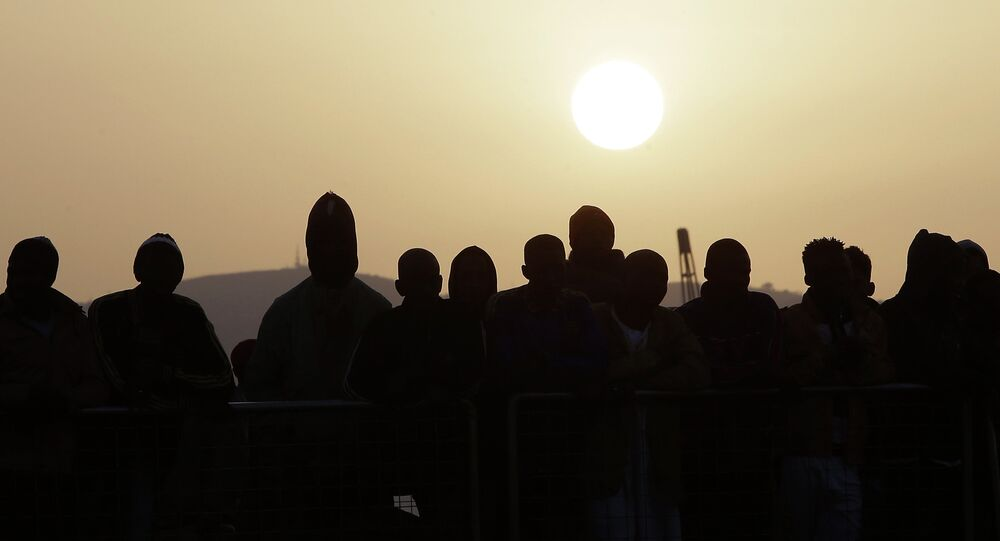 Migrants wait to disembark from the Iceland Coast Guard vessel Tyr, at the Messina harbor, Sicily, southern Italy