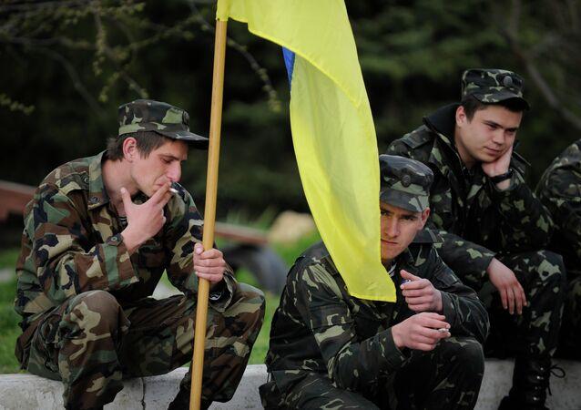 Ukrainian servicemen hold a Ukrainian flag before leaving the Belbek airbase near Sevastopol, Crimea, Friday, March 28, 2014