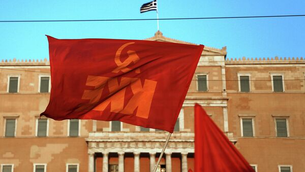 A Greek Communist Party flag waves in front of the Parliament in Athens during an protest against any military action by the U.S. and its allies against Syria, Thursday Aug. 29, 2013 - Sputnik International
