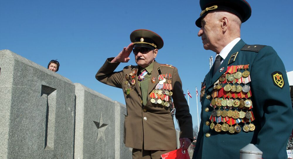 WWII veterans salute in front of the World War II monument in Riga on May 9, 2013 during Victory Day celebrations