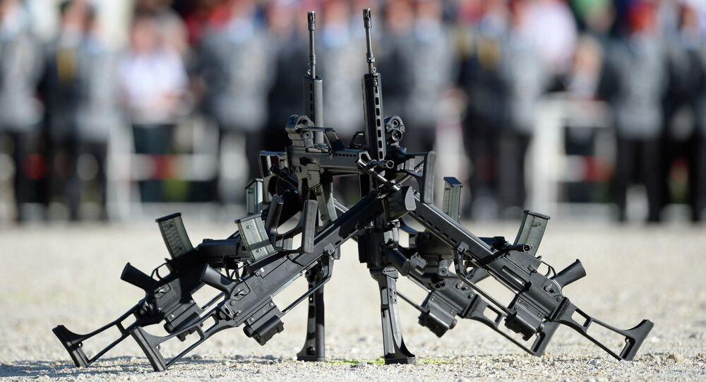 FILE - In this June 5, 2014 file photo G36 rifles of manufacturer Heckler&Koch stand in front of soldiers in Sigmaringen, southern Germany