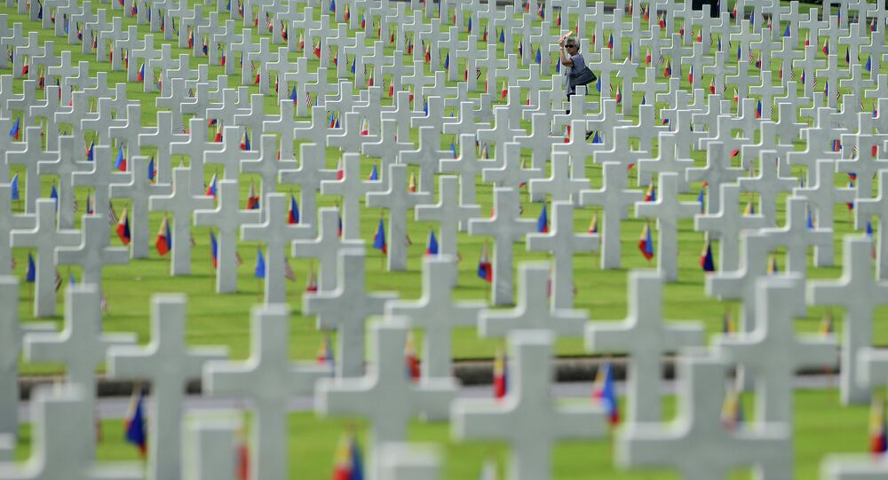 A woman walks amongst the graves of soldiers who fell during World War II, searching for a grave of a relative during a service to mark US Memorial Day at the Manila American Cemetery