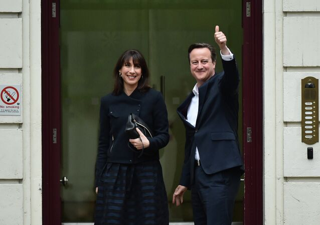 British Prime Minister and Leader of the Conservative Party David Cameron (R) and his wife Samantha arrive at Conservative Party headquarters in London on May 8, 2015,