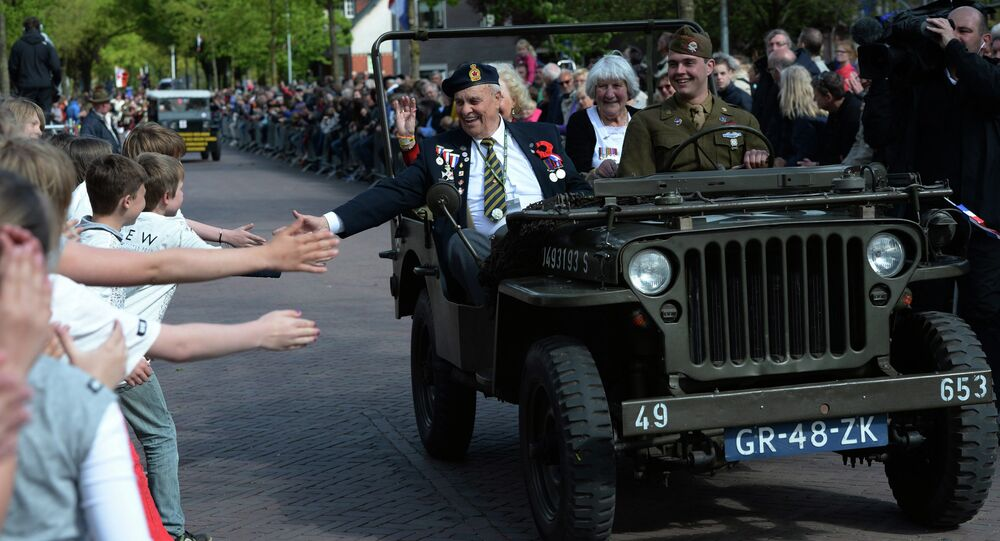 Children reach out to touch the hand of Canadian World War II navy veteran Bert Reynolds, 88, as he takes part in a parade to celebrate the 70th anniversary of the Liberation of the Netherlands in Wageningen, Netherlands on Tuesday, May 5, 2015