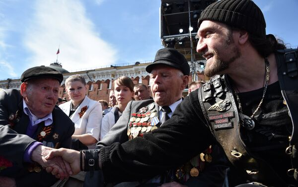 Alexander Zaldostanov also known as Khirurg (The Surgeon), leader of the Night Wolves bikers' club, shakes hands with a veteran before the Victory Day military parade at Red Square in Moscow on May 9, 2015 - Sputnik International