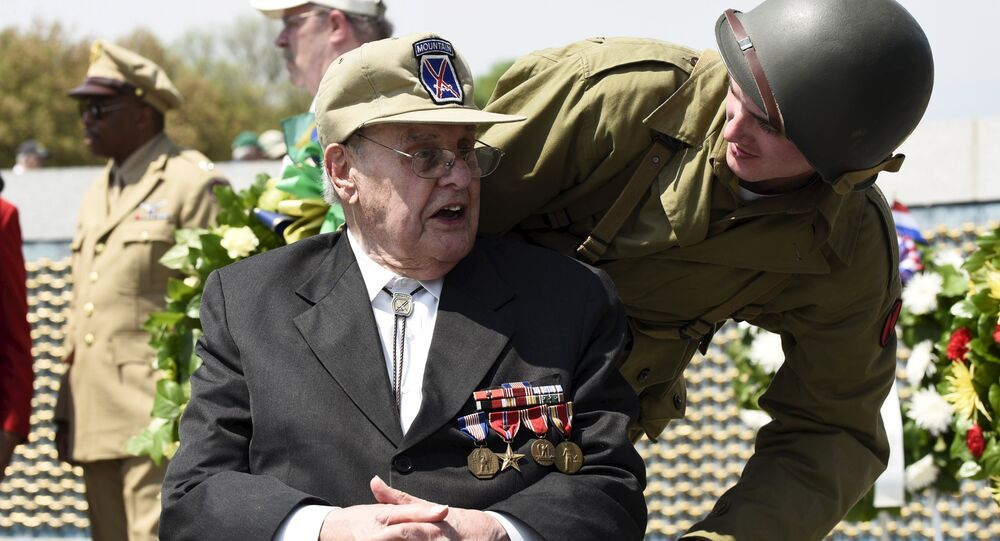 A veteran interacts with an usher dressed in World War II era uniform during a Capitol Flyover over the National Mall to commemorate the 70th anniversary of VE (Victory in Europe) Day, in Washington May 8, 2015