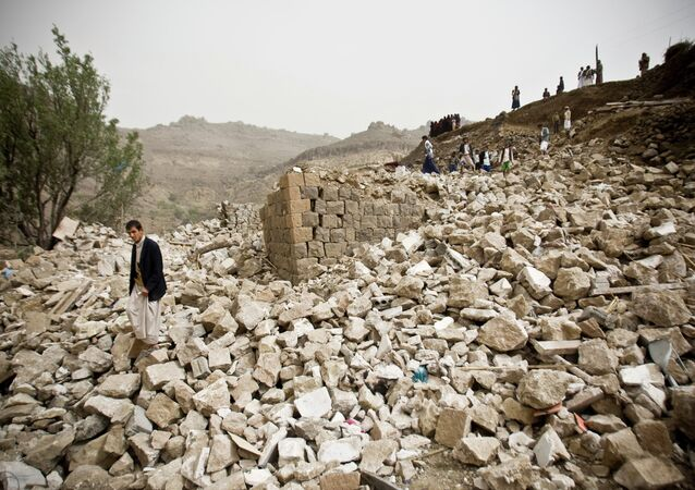 Yemenis search for survivors in the rubble of houses destroyed by Saudi-led airstrikes in a village near Sanaa, Yemen