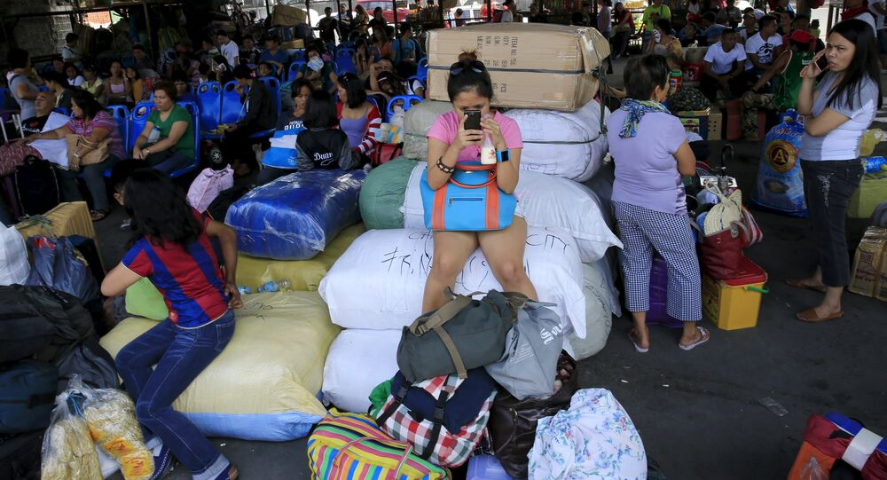 Stranded passengers guard their belongings while waiting at a bus terminal in Manila May 9, 2015. The Philippines on Saturday evacuated thousands of people in the northeastern part of its main island of Luzon on Saturday, less than 24 hours before a powerful typhoon was expected to make landfall