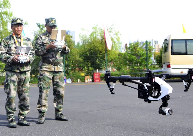A pair of militia members fly drones during a test in Shanghai, China, April 21, 2015.