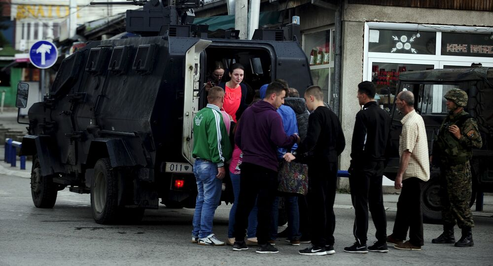 People are evacuated with an armored vehicle near a police checkpoint in Kumanovo, Macedonia, May 9, 2015