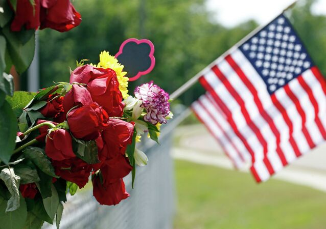 An American flag hangs next to bouquets of flowers on a barbed wire fence Sunday, May 10, 2015, at a makeshift memorial near the site where two Hattiesburg, Miss., police officers were shot to death during a Saturday evening traffic stop