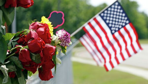 An American flag hangs next to bouquets of flowers on a barbed wire fence Sunday, May 10, 2015, at a makeshift memorial near the site where two Hattiesburg, Miss., police officers were shot to death during a Saturday evening traffic stop - Sputnik International