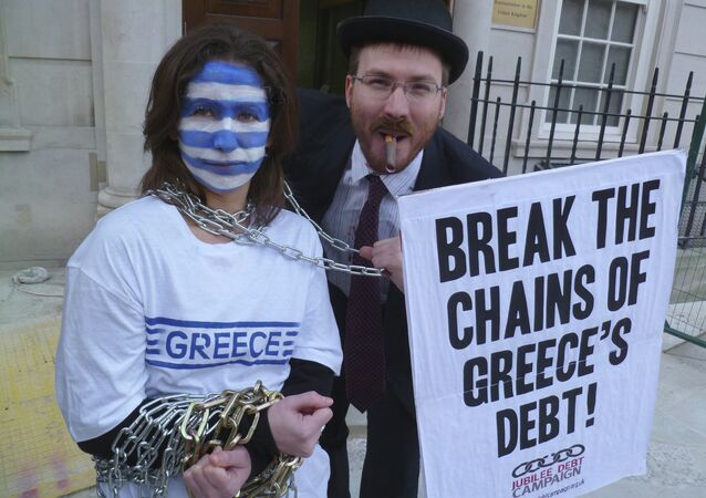 Campaigners from Jubilee Debt Campaign UK dressed as bankers hold Greece in chains outside the European Commission in London to demand debt cancellation for Greec, 20 February 2012.