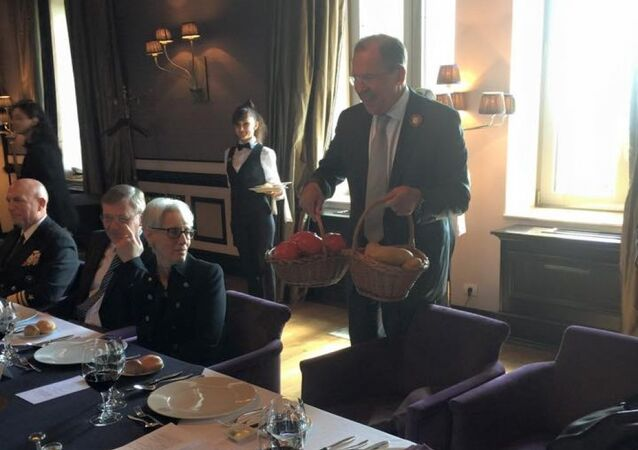 Russian Foreign Minister Sergei Lavrov gives two baskets of vegetables from Sochi gardens to his US counterpart John Kerry