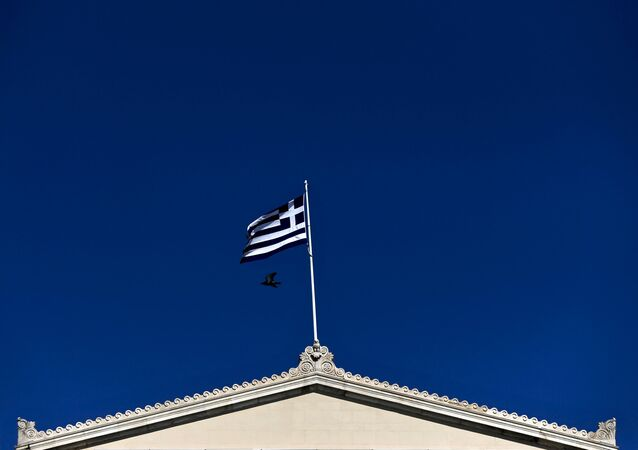 A Greek national flag flutters atop the parliament building in Athens