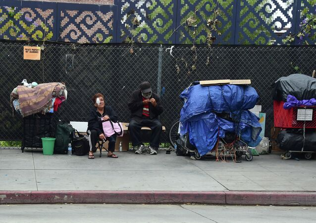 Homeless residents sit beside their belongings in downtown Los Angeles