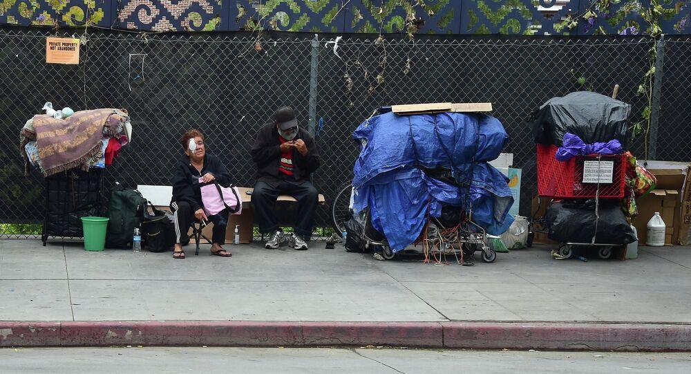 Homeless residents sit beside their belongings in downtown Los Angeles