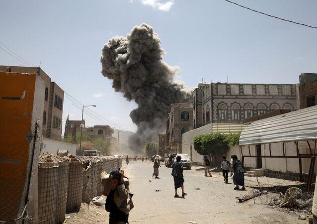 People flee as smoke billows after air strikes hit the house of Yemen's former President Ali Abdullah Saleh in Sanaa May 10, 2015