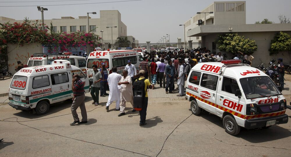 Ambulances and people gather gather outside the hospital after an attack on a bus in Karachi, Pakistan, May 13, 2015
