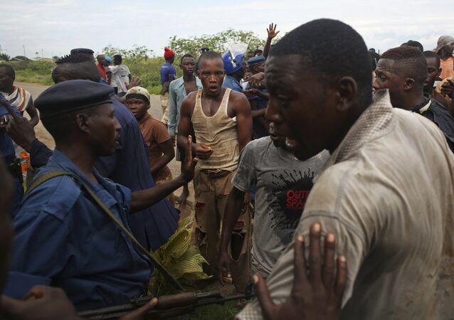 Protesters gesture near female police officer accused of shooting a protestor in Buterere neighbourhood of Bujumbura, Burundi