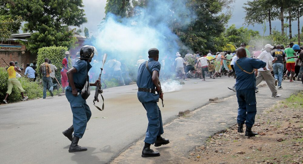 Demonstrators trying to march to the town center flee as police disperse them with tear gas, in the Ngagara district of Bujumbura, Burundi Wednesday, May 13, 2015