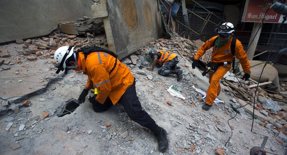 Nepalese military personnel and International rescue check on a collapsed building after an earthquake in the centre of Kathmandu, Nepal