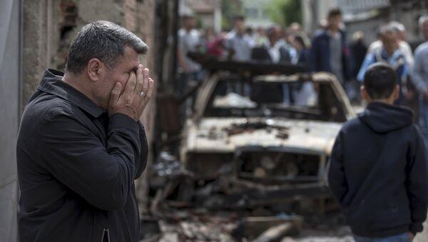 A man reacts next to a burnt out vehicle in Kumanovo, Macedonia - Sputnik International