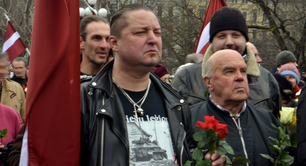 The shirt this man is wearing has written Latvian Legion..., an a picture of a Nazi tank with the Latvian Legion badge at the bottom right.
