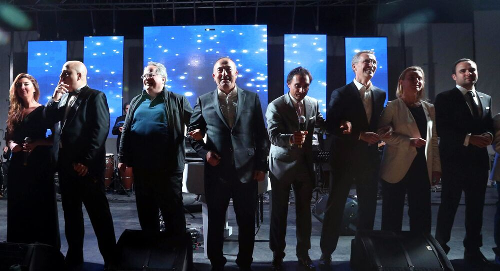 Secretary General of NATO, Jens Stoltenberg, third right, Turkish Foreign Minister Mevlut Cavusoglu, center, Greek Foreign Minister Nikos Kotzias, third left, EU High representative for foreign policy Federica Mogherini, second right, and other NATO officials dance to We are the world  after a dinner during the NATO Foreign Ministers' conference in Antalya, Turkey, Wednesday, May 13, 2015